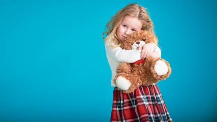 Fabulous little girl hugging brown teddy bear.