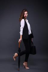 Pretty female business lady in a black jacket white shirt, umbrella, handbag on a dark background. Studio shot
