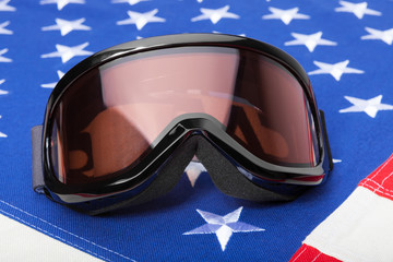 Winter sport goggles over USA flag