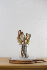 Vintage silverware in jar and cutting boards on wooden table