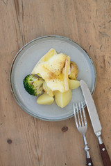 Plate with boiled potatoes and broccoli covered with melted raclette cheese on wooden background