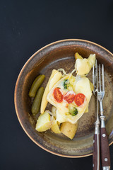 Plate with boiled potatoes and pickles covered with melted raclette cheese with cheery tomatoes and broccoli