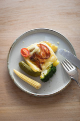 Plate with boiled potatoes, broccoli and pickles covered with melted raclette cheese with grilled bacon slice