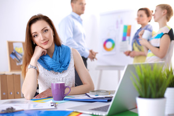 Portrait of attractive female  designer sitting on desk  in office