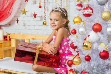 Smiling girl sitting on a bench with a huge gift from the Christmas trees