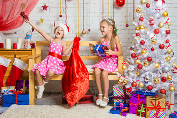 Two girls having fun and happy New Year gifts from Santa Claus bag
