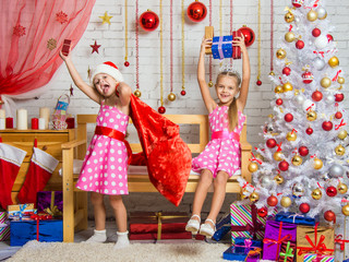 Two girls having fun and happy New Years gifts in a homelike atmosphere of the New Year