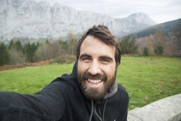 chico con barba haciendose un selfie en la montaña