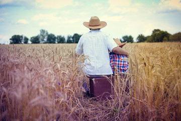 Backview of happy family sitting on old suitcase in farm field