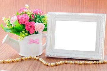 Flowers vase and vintage white picture frame on wooden desktop.