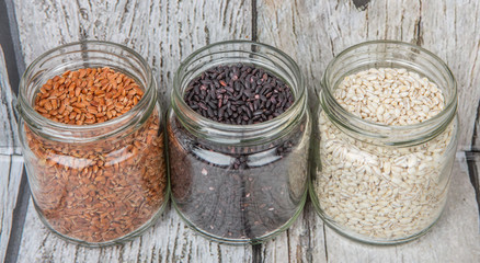 White, brown, black millet in mason jars over wooden background