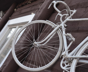 White bike hanging on the wall,
