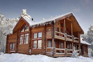 Log home winter with large windows, balcony and porch, daytime.