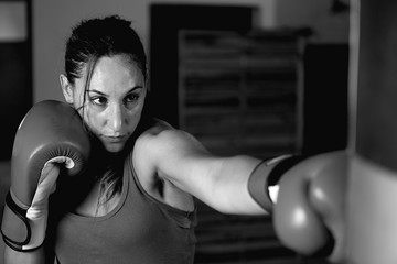 Close-up of young female boxer practicing in gym