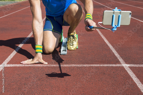 Athlete crouching at the starting line of a running track