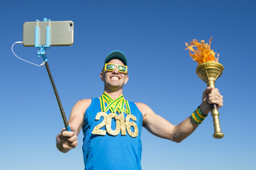 Gold medal 2016 athlete smiling for a selfie with a sport torch against bright blue sky