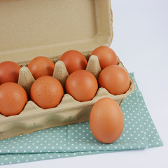 The fresh hen eggs on the paper panel box and the cotton fabric.