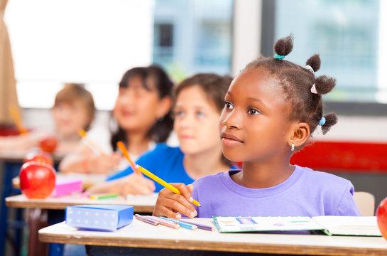 Happy children in a multi ethnic elementary classroom