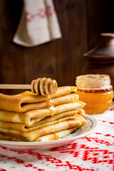 Stack of crepes or pancakes served with honey (Russian cuisine - blini, blintzes, national food for Maslenitsa)