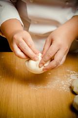 Woman's hands knead dough. Selective focus. Toned
