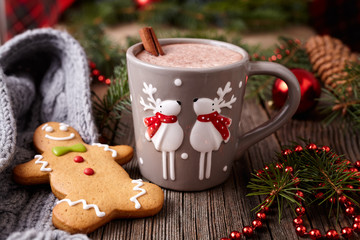 Cup of hot chocolate or cocoa drink with two cute deer, cinnamon and gingerbread man christmas cookies in new year tree decorations frame on vintage wooden table background. Homemade recipe.