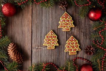 Christmas gingerbread fir trees cookies composition in christmas decorations frame on vintage wooden table background. Traditional homemade dessert recipe.