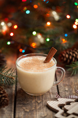 Eggnog traditional christmas holiday egg, vanilla, rum alcohol liqueur drink preparation recipe in two glass cups with cinnamon sticks on wooden vintage table. Colorful bokeh background. shallow depth