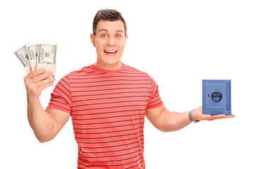 Cheerful guy holding money and a small safe