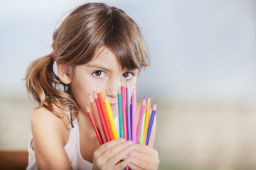 Little happy hiding her face with colored pencils