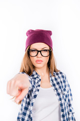 serious student girl in a cap points index finger at the camera