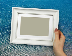 Wooden frame in woman hands on the Sea water background