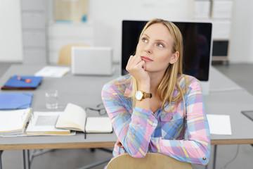 junge frau im büro sitzt am schreibtisch und denkt nach