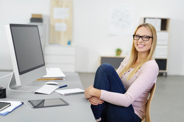 lachende junge geschäftsfrau sitzt lässig im büro