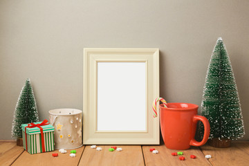 Poster frame mock up template for Christmas holiday greeting presentation with cup and small pine trees