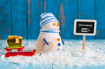 Word January written on direction sign and Snowman with red sled With new year gift. New Year decorations