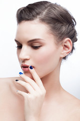 Beautiful young brunette girl posing in the studio. Natural fresh daily makeup, blue nails.