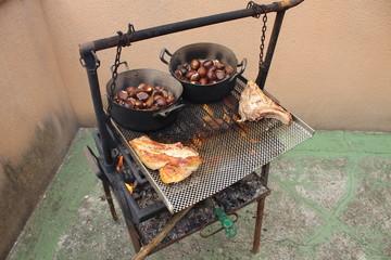 Cocinando carne y castañas a la brasa