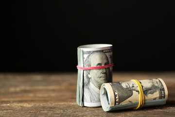 Dollars roll on wooden table in front of dark background