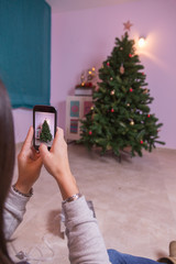woman photographing Christmas tree