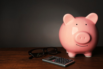 Piggy bank and calculator on table , gray background