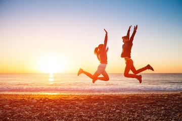 Couple jumps on the beach over sunrise