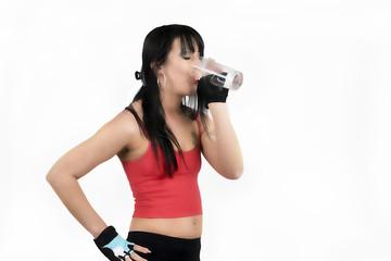Junge Frau trinkt Wasser beim Sport.