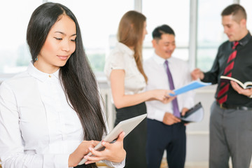 Successful asian business woman holding tablet PC