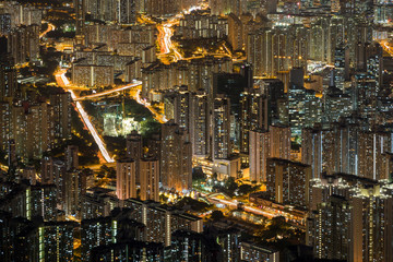 Lit apartment buildings in New Kowloon viewed from above at night in Hong Kong, China.