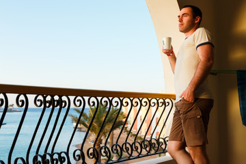 handsome guy standing on balcony