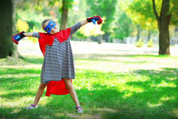 Happy little girl dressed as superhero in boxing gloves at the park