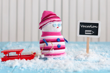 Vacation concept background. Snowman with red sled stand near direction sign vacation