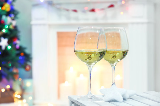 Wine glasses with Christmas decor on fireplace background