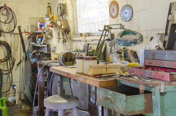 A very messy workshop with a huge variety of tools, work bench, lamp and much more.