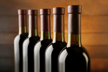 Wine bottles in a row on wooden background, close up